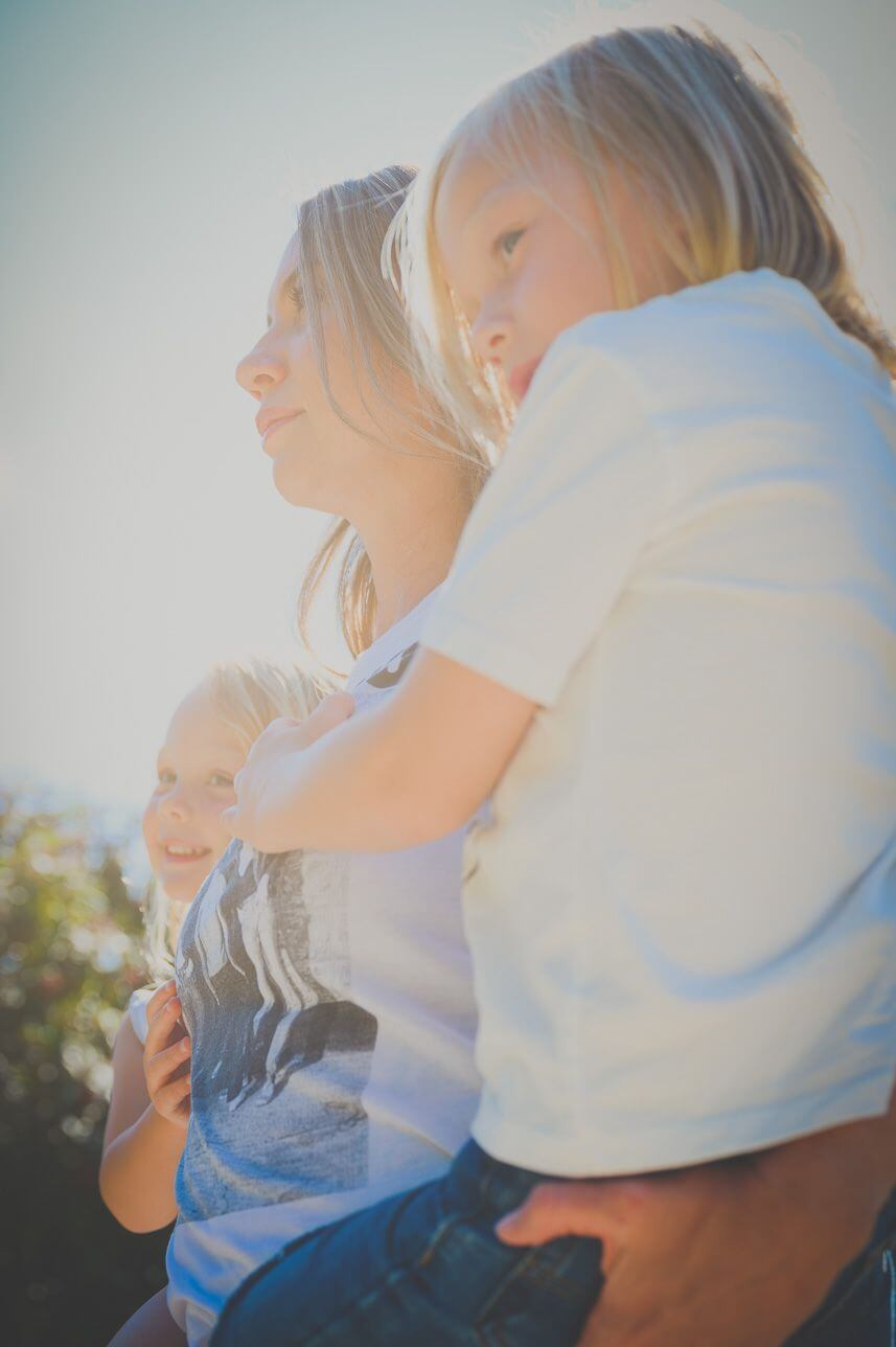 Sarah holding her two children, smiling in the sunlight.