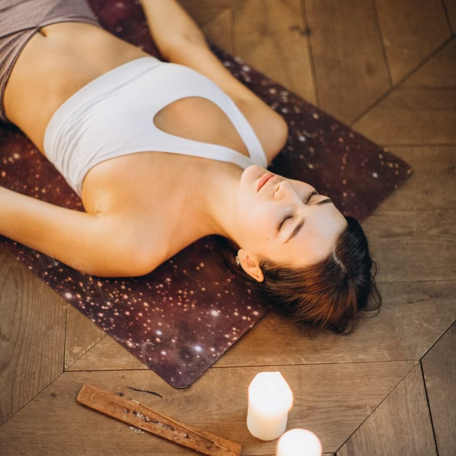 A woman laying on a yoga mat next to candle and incense.