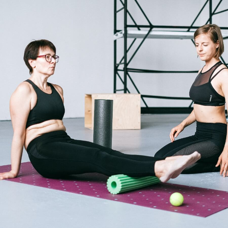 two women practicing gentle yoga with the help of a bolster under the students legs.